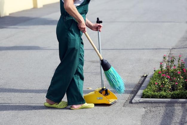 O zelador varrendo a rua das vassouras Foto Premium
