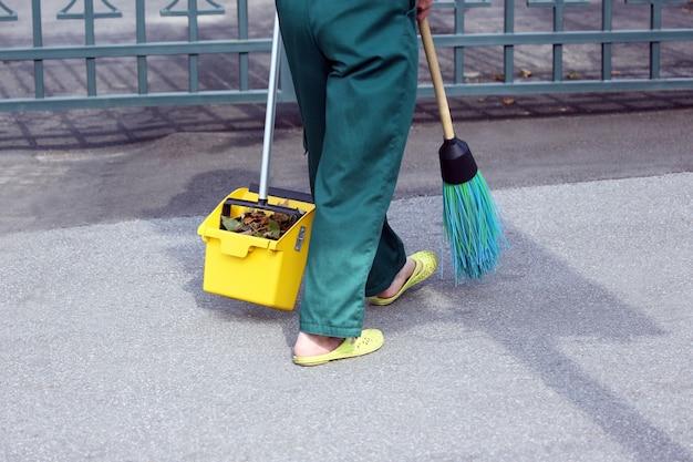 O zelador varreu a calçada da cidade com as folhas caídas Foto Premium
