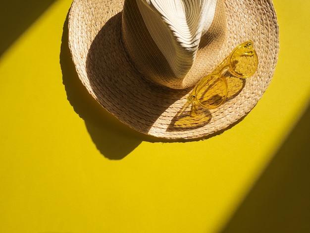 Objetos de proteção solar. chapéu de palha mulher com óculos de sol amarelo na vista amarela Foto Premium
