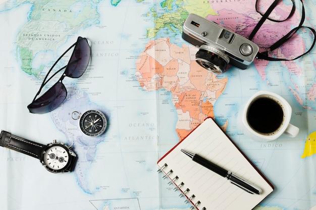 Objetos de viagem de vista superior no fundo do mapa Foto gratuita