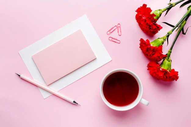 Objetos vermelho-rosa. o copo do chá, cravo floresce o bloco de notas para o texto no fundo do rosa pastel. Foto Premium