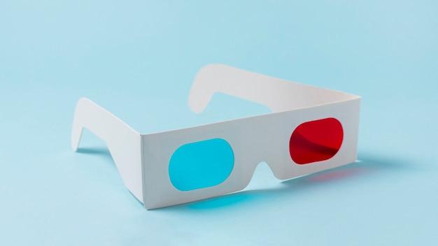 Óculos 3d de papel branco vermelho e azul sobre fundo azul Foto gratuita