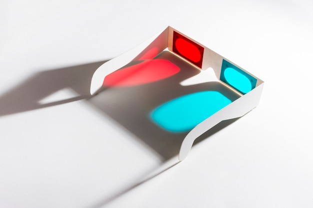 Óculos 3d vermelhos e azuis em fundo reflexivo Foto gratuita
