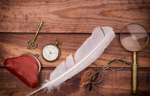 Óculos antigos perto de relógio de bolso, penas, lupa, bolsa vintage e chave Foto Premium
