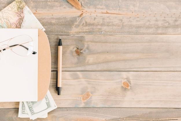 Óculos; bloco de anotações; moeda; mapa e caneta no fundo da prancha de madeira Foto gratuita