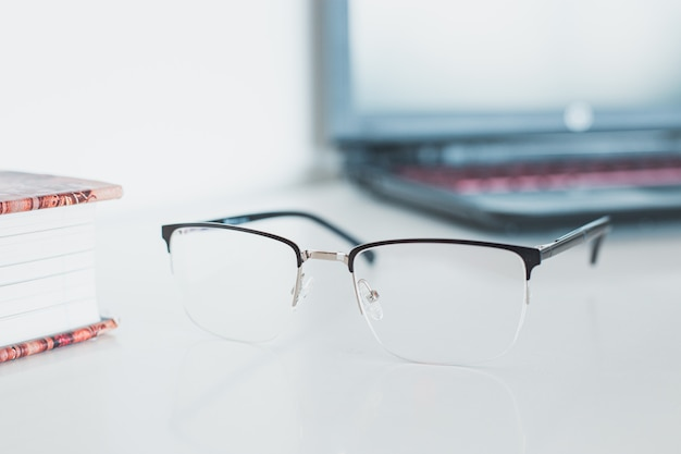 Óculos com livro e computador portátil Foto Premium