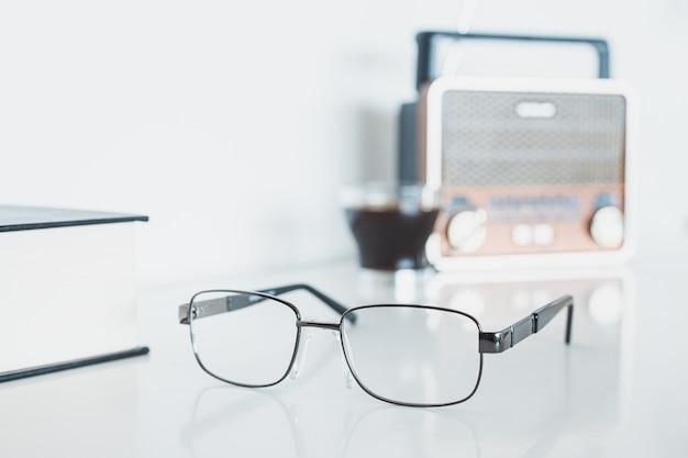 Óculos com rádio, livro e café Foto Premium