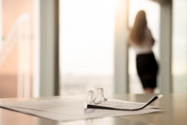 Óculos corretivos para leitura na mesa, silhueta feminina no fundo Foto gratuita