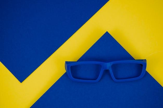Óculos de crianças azuis sobre fundo azul e amarelo Foto gratuita