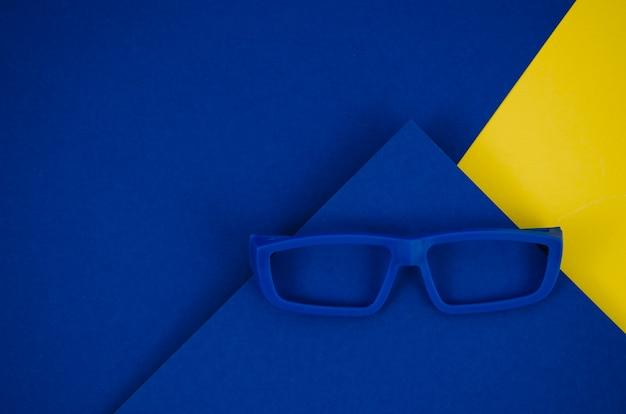 Óculos de crianças azuis sobre fundo colorido Foto gratuita