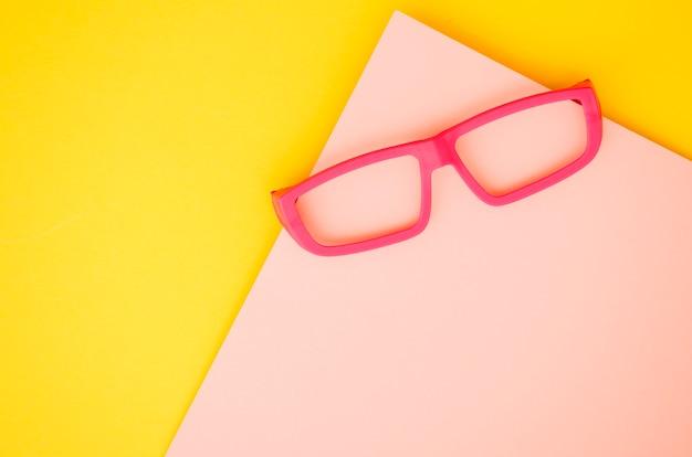 Óculos de crianças rosa sobre fundo rosa e amarelo Foto gratuita