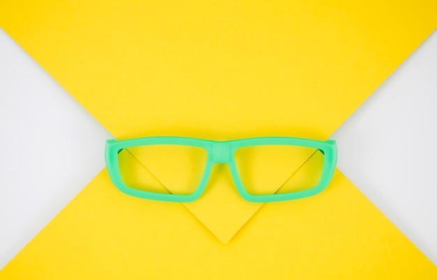 Óculos de crianças verdes em fundo colorido Foto gratuita
