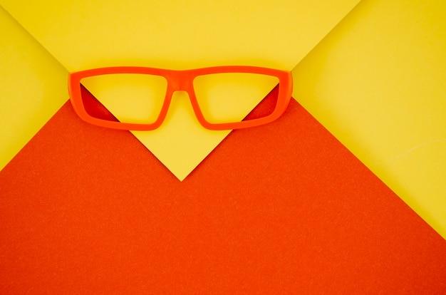 Óculos de crianças vermelhas sobre fundo vermelho e amarelo Foto gratuita