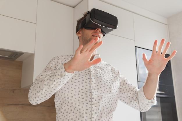 Óculos de homem barbudo usando realidade virtual no estúdio moderno de coworking. smartphone usando com fone de ouvido vr. horizontal, desfocada Foto Premium