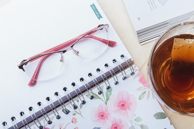 Óculos de mulher com chá e livros Foto Premium
