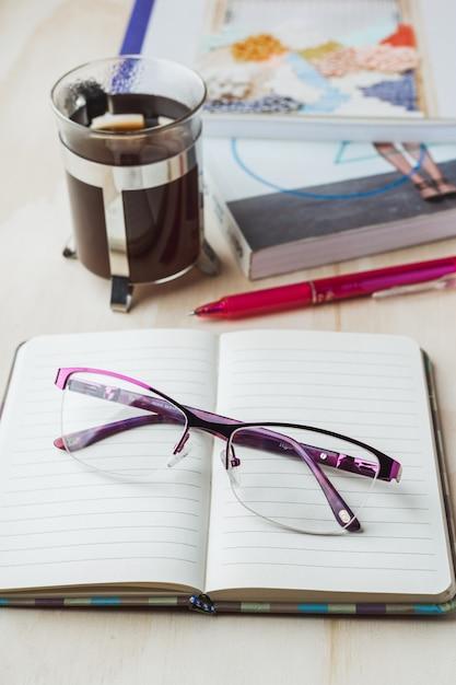 Óculos de mulher com notebook, café, lápis e livro Foto Premium