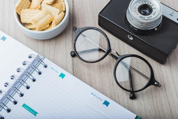 Óculos de mulher com planejador, biscoitos e câmera Foto Premium