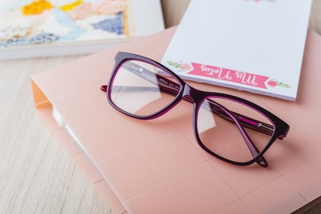Óculos de mulher com planejador e livros Foto Premium