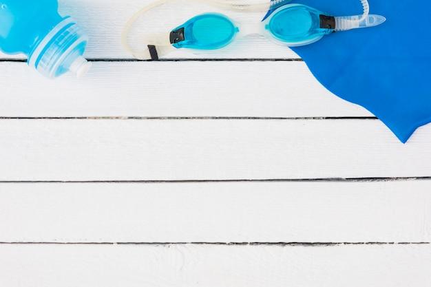 Óculos de natação azuis; garrafa de água e guardanapo na mesa de madeira branca Foto gratuita