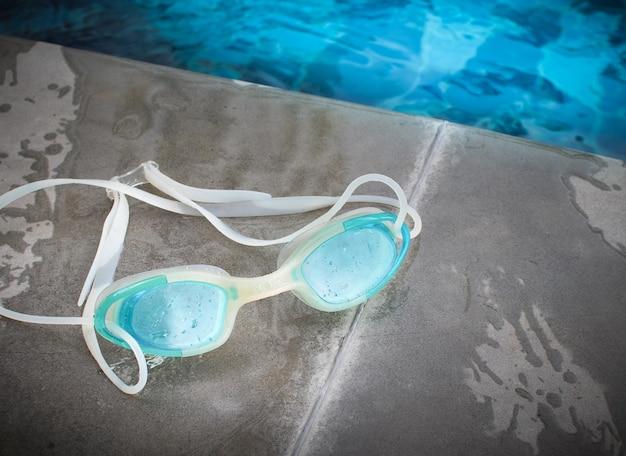 Óculos de natação modernos azuis colocados ao lado da piscina. Foto Premium