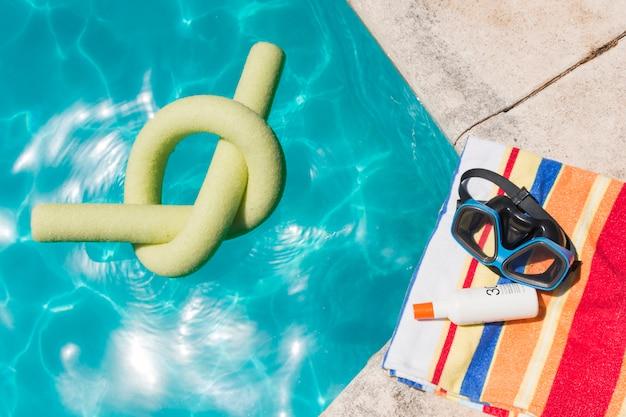 Óculos de proteção com loção na toalha perto da piscina Foto gratuita