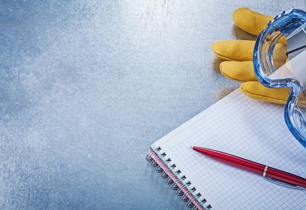Óculos de segurança luvas de couro caderno caneta na mesa metálica Foto Premium