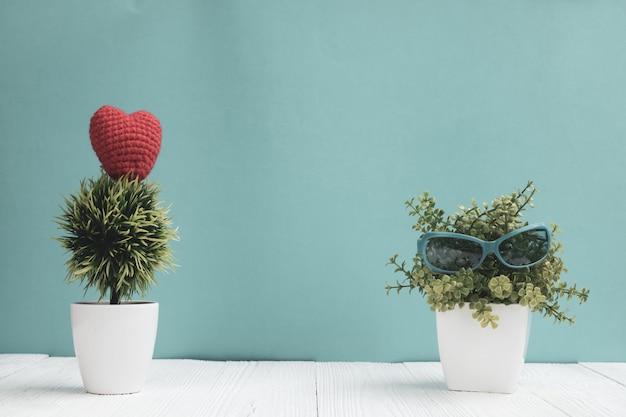 Óculos de sol azuis com pequena árvore de decoração em vaso branco e coração vermelho Foto Premium