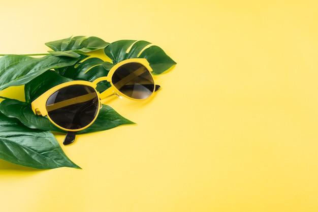 Óculos de sol com folhas verdes artificiais sobre fundo amarelo Foto gratuita