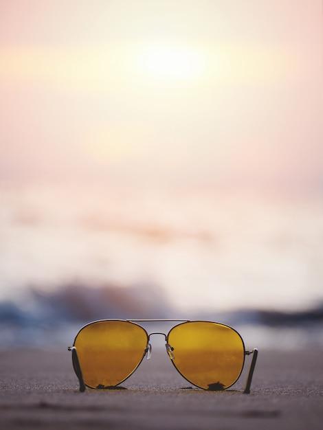 Óculos de sol com lente amarela na areia na praia do sol. Foto Premium