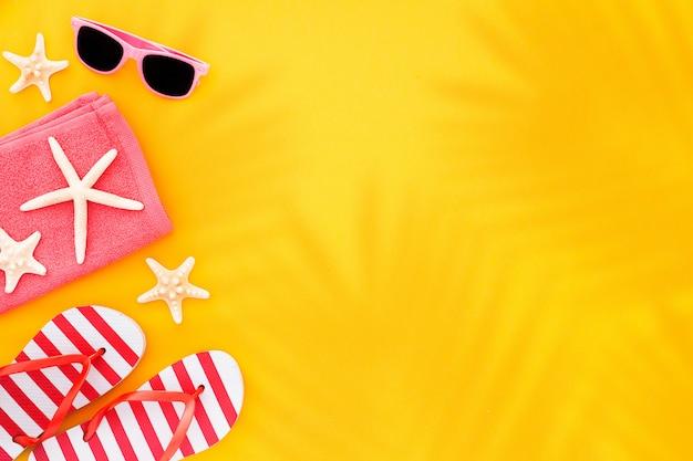 Óculos de sol da vista superior, estrela do mar de toalha e falhanços de aleta, no amarelo com luz solar e na sombra das folhas de palmeira. Foto gratuita