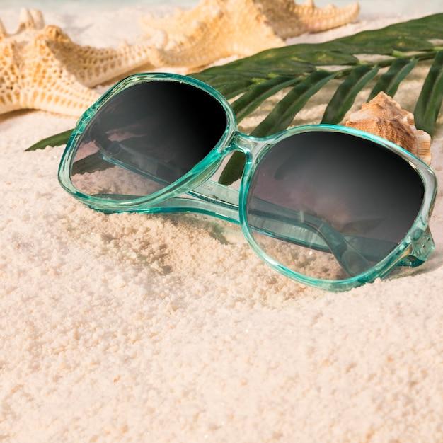 Óculos de sol deitado na praia de areia Foto gratuita