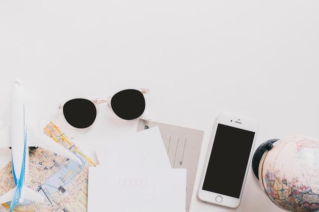 Óculos de sol e smartphones perto de mapas Foto gratuita