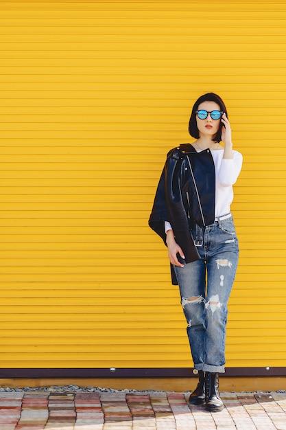 Óculos de sol linda garota no fundo amarelo brilhante Foto Premium