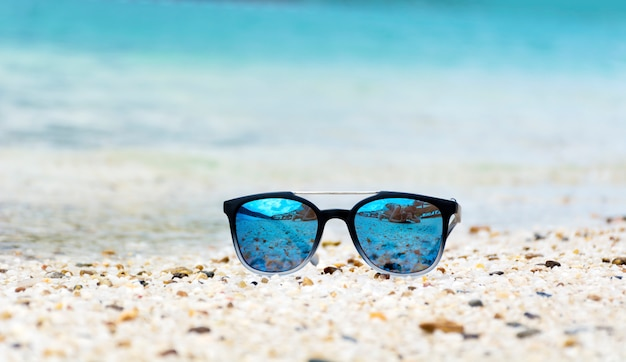 Óculos de sol na areia Foto gratuita