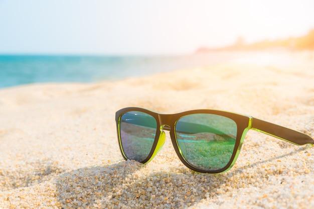 Óculos de sol na costa arenosa. conceito de verão. Foto Premium