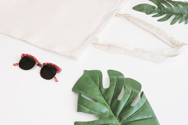 Óculos de sol, saco de algodão e monstera verde sobre fundo branco Foto gratuita