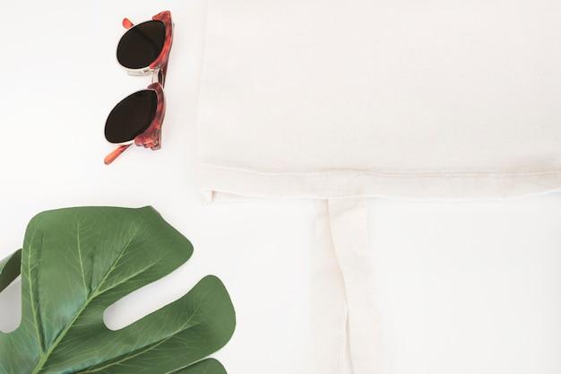 Óculos de sol, saco de pano branco e folha de monstera no fundo branco Foto gratuita