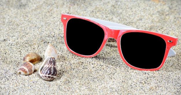 Óculos de sol vermelhos na areia Foto Premium