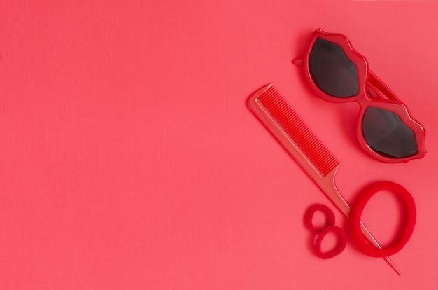 10b5b85ee Óculos de sol vermelhos, pente, elásticos de cabelo. fundo vermelho ...
