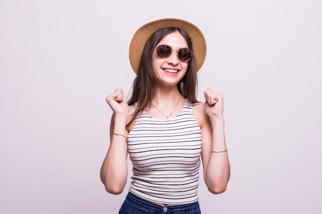 Óculos de sol vestindo do chapéu da mulher chinesa que estão sobre o fundo branco isolado que comemora surpreendido e surpreendido para o sucesso com os braços levantados e os olhos abertos. conceito vencedor. Foto gratuita