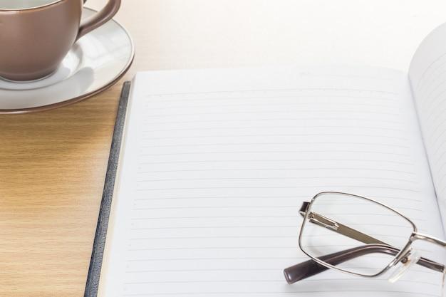 Óculos e bloco de notas com a página em branco Foto Premium