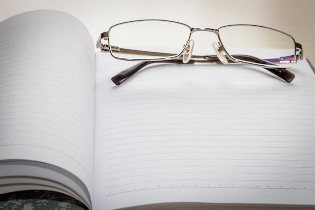 Óculos e bloco de notas com página em branco Foto Premium