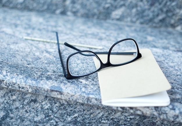 Óculos e um caderno, com uma caneta, repousam na escada de um prédio de escritórios. Foto Premium