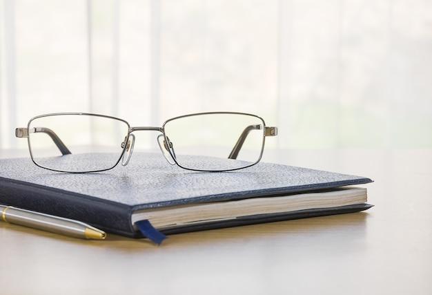 Óculos e um livro na mesa Foto Premium
