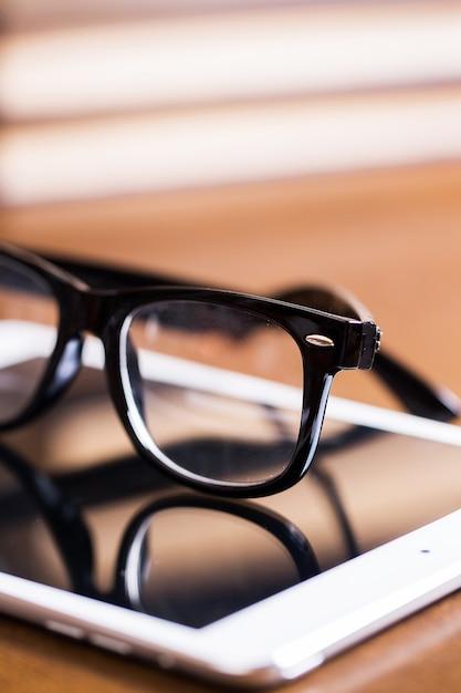 Óculos e um tablet Foto gratuita