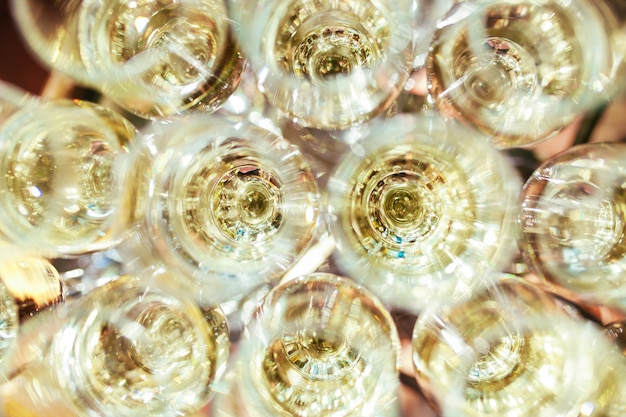 Óculos elegantes com champanhe em pé em uma fila na mesa servindo durante a festa ou celebração Foto Premium