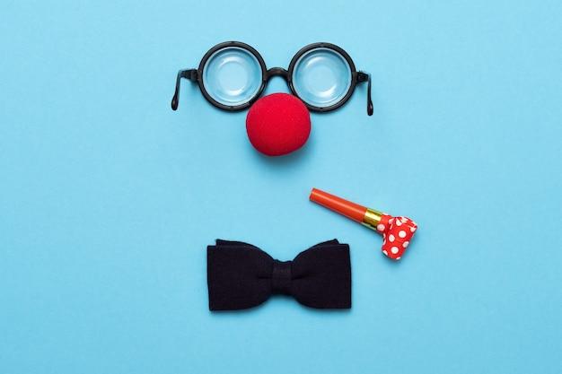 Óculos engraçados, nariz de palhaço vermelho e gravata repousam sobre um fundo colorido, como um rosto Foto Premium