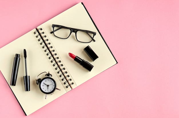 Óculos escuros, despertador, bloco de notas de papel, rímel e pomada vermelha na superfície rosa. Foto Premium