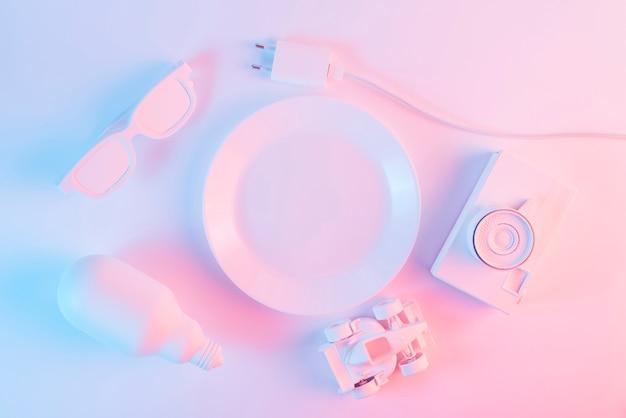 Oculos escuros; lâmpada; carro de fórmula um; plugue elétrico e câmera em fundo rosa e azul Foto gratuita