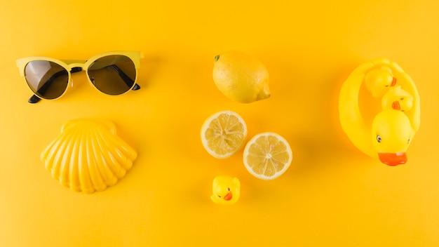Oculos escuros; vieira; pato de limão e borracha em pano de fundo amarelo Foto gratuita